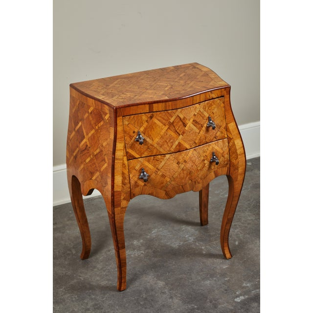 An early 20th century petite Italian Marquetry chest of drawers. Gorgeous dark hardware on two functioning drawers.