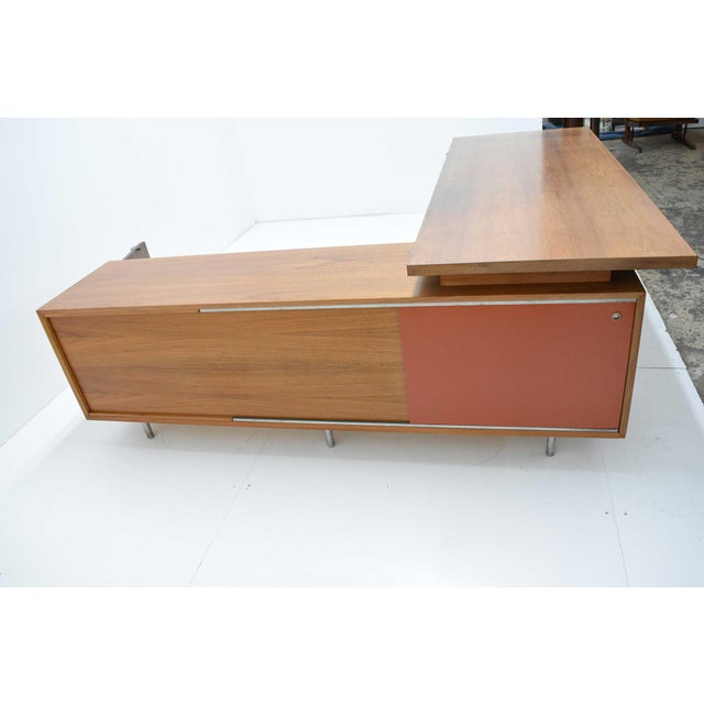 Executive L-shaped desk with original wood grained laminate writing surface, two sided credenza with red masonite sliding...