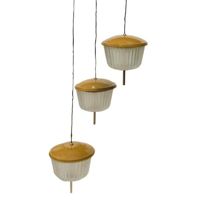 Italian modern three-light chandelier, c. 1970s, each encased in painted gold metal and frosted glass shades. In need of...