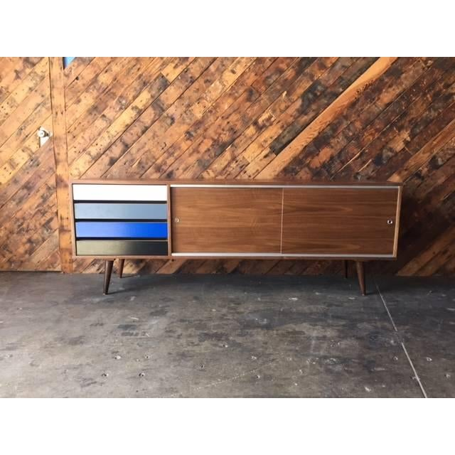 Newly built, custom, Mid-century-style credenza. Crafted from walnut wood, this piece features a playful stack of cool-hue...