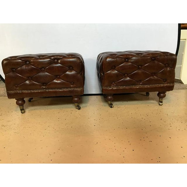 A pair of leather Chesterfield Ralph Lauren style footstools. Each having casters on mahogany feet supporting a tufted and...