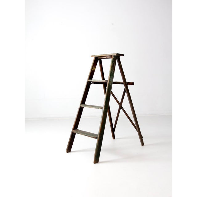 A vintage wood folding ladder. Beautifully aged, the green painted ladder has a striking patina and great old hardware. It...