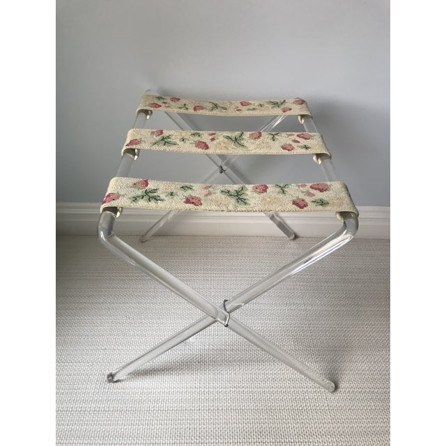 This is a lucite luggage rack with original needlepoint straps. The three straps are of strawberries and yellow geraniums....