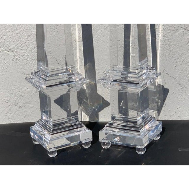 A monumental pair of footed Lucite obelisks, each one of typical form, tall, sleek and clear, a rare size.
