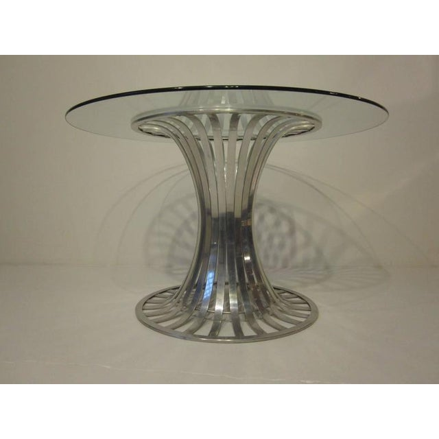 An aluminium banded tulip styled dining table with plate glass top, a lite airy look with a dash of Modern.