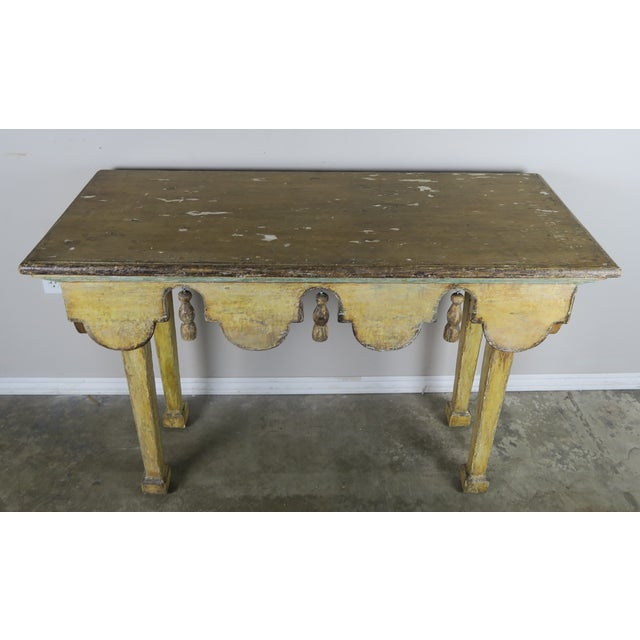 Painted Italian midcentury table with swags and carved tassels hanging between each swag. The table stands on four...