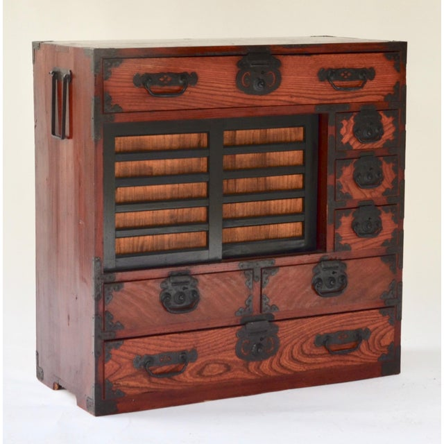 Antique Japanese choba tansu (merchant's chest) made of keyaki wood in a warm reddish brown lacquer finish. Each drawer...