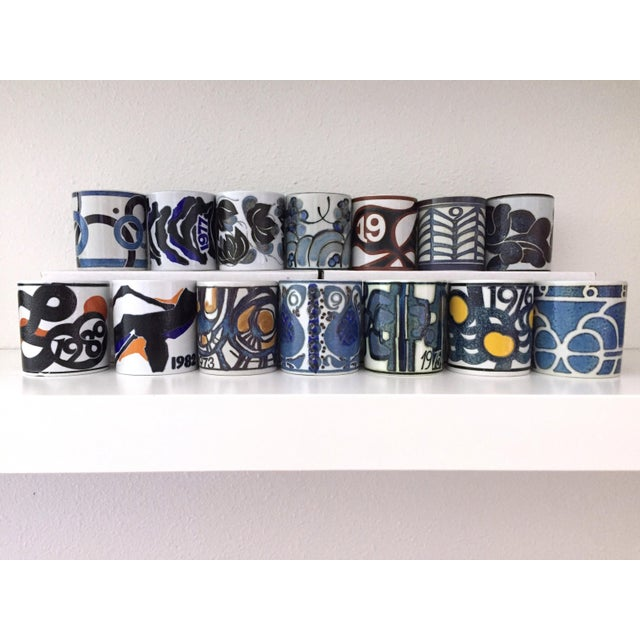 This is for a set of fourteen annual mugs by Royal Copenhagen. Each year a different artist was invited to design a...