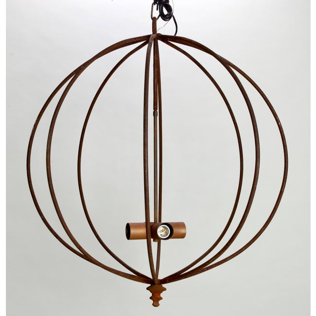 Circa 1970's large open frame iron sphere light fixture found in France. Surface finish is dark with rust colored patina....