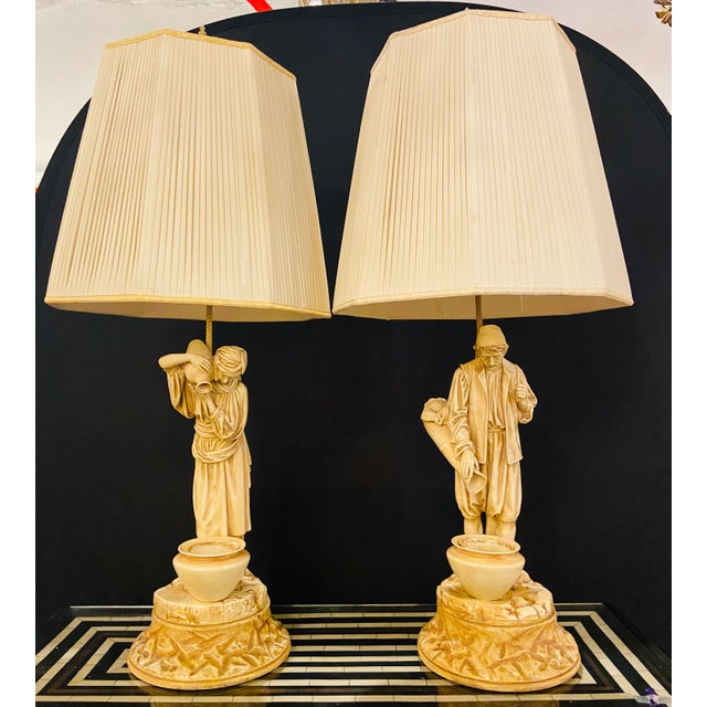 A Pair of Arab Water Bearers in a Finely Cast Porcelain Finish, Table Lamps. Pots with inserts. Includes shades A pair of...