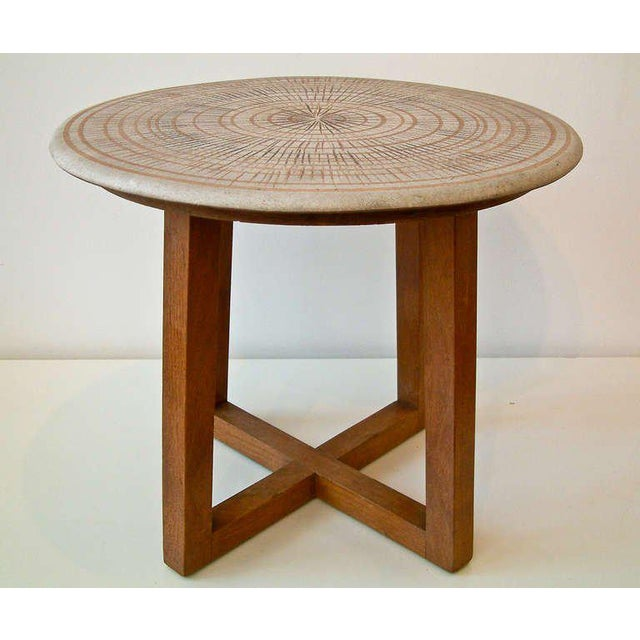 United States Circa 1950 A circular ceramic top table with a matte glazed concentric circle motif supported by a walnut base.
