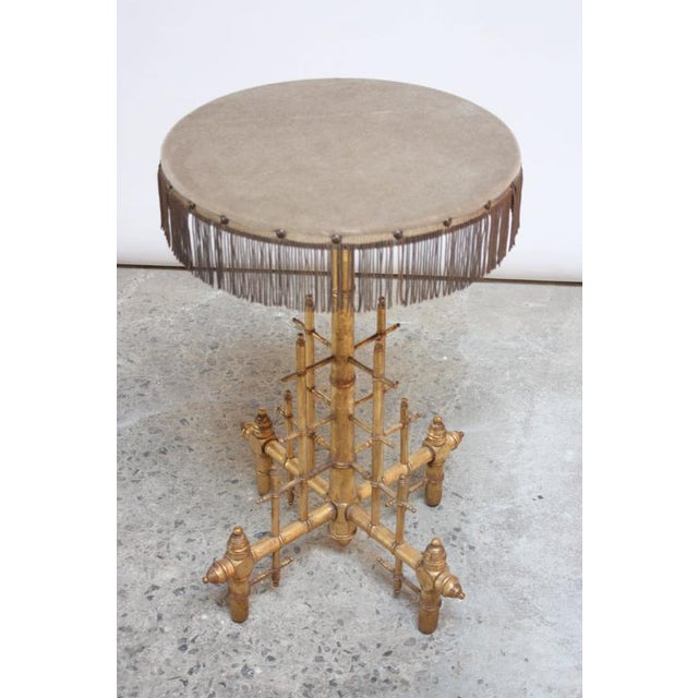 Unique and whimsical drum table comprised of a gilded wooden base depicting pipes and fittings. The original textile was...