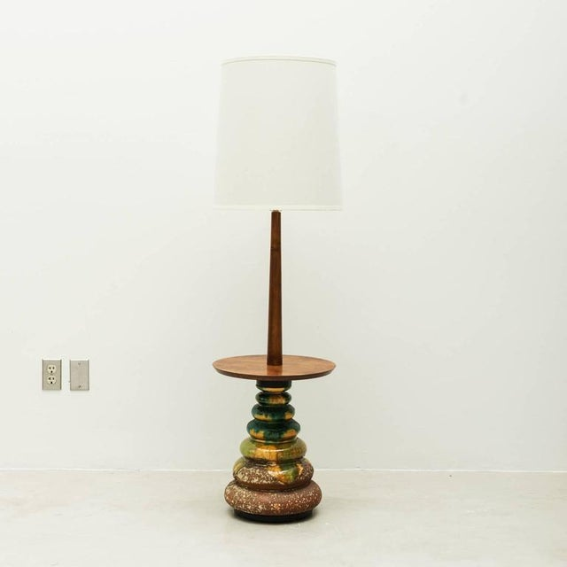 Floor lamp with a beautiful, organic studio ceramic base. Brown base glaze with green, yellow and white drip glaze on a...