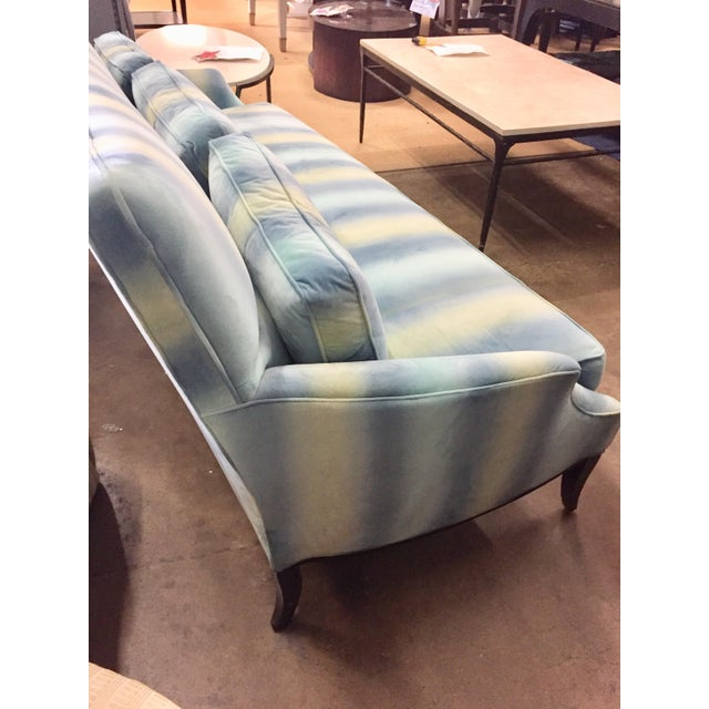 High end Caracole Sofa will brighten any room. Different hues of blue lines and a pop of lime green upholstesr the sofa.