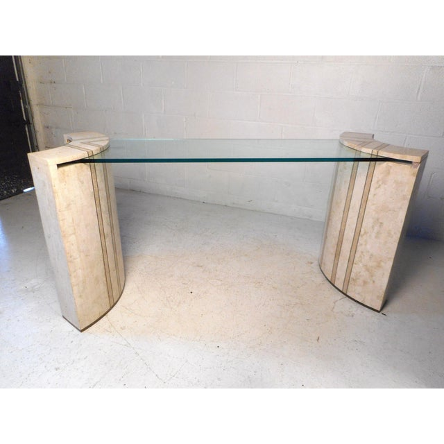 This unique midcentury hall table features a two-piece tessellated marble base with brass trim at the bottom, a thick pane...