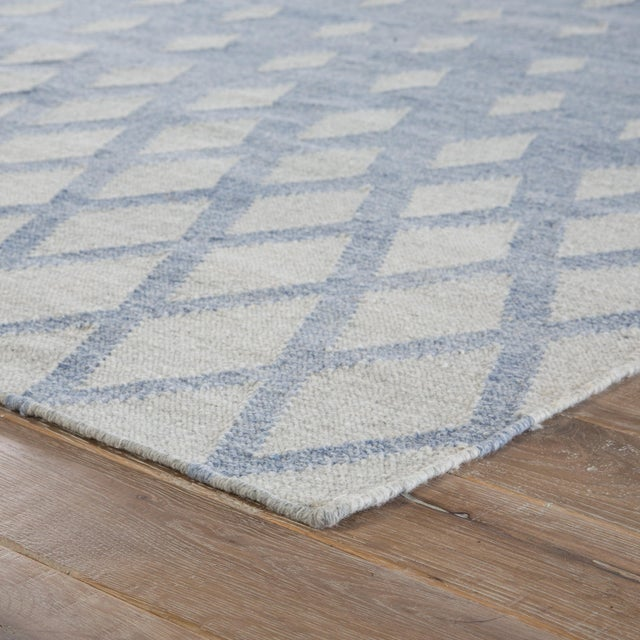 This dhurrie-style area rug infuses both indoor and outdoor spaces with a contemporary touch of geometric patterning. A...