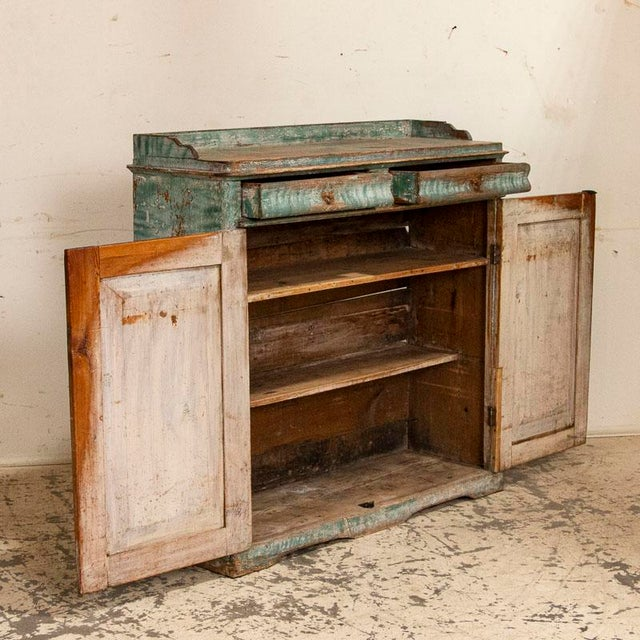 The delight one finds in this rare sideboard is due to the original folk art painted finish. A mix of white and aqua green...