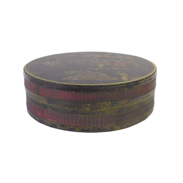This decorative wooden flat round box is painted with black lacquer on the surface and oriental scenery is precisely drawn...