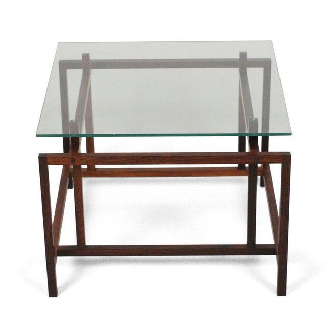 A pair of square cocktail tables with glass tops that fit the exact proportions of the elegantly engineered structures...