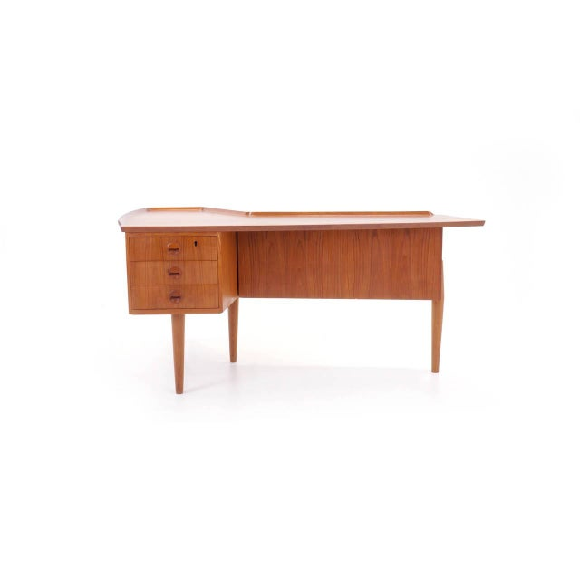 Great design Arne Vodder desk. Wonderful configuration of drawers, built in bar and sliding panel revealing storage.