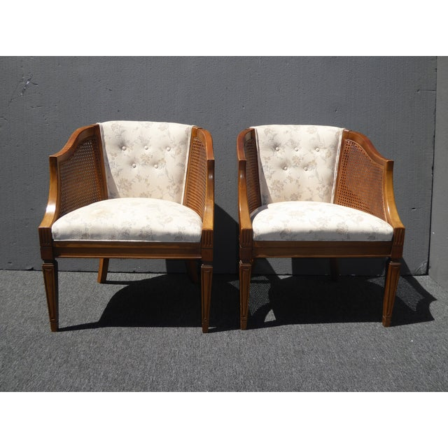 Pair Vintage French Country wood and cane white tufted accent club chairs. On one seat there is a stain and a tear....