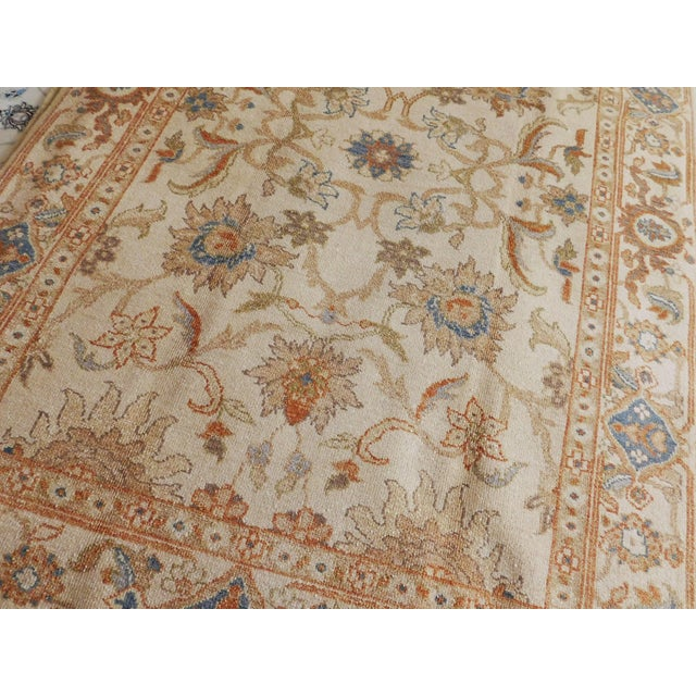 Hand knotted. Wool pile on cotton foundation. Stylized flowers on beige field , within beige border decorated with...