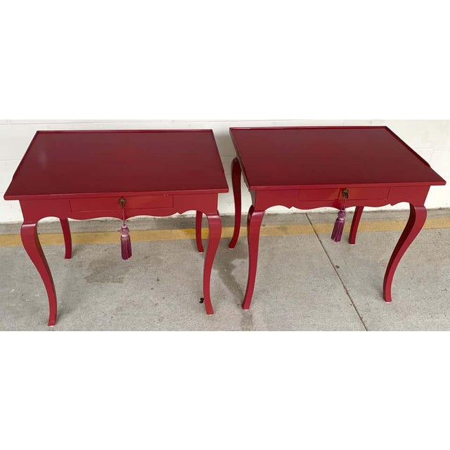 Pair of bold mauve lacquered end/ nightstands tables, each one neoclassical in style with slight gallery edge top, fitted...