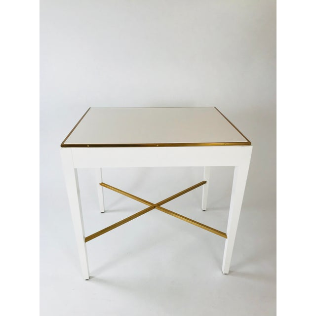 Generously proportioned side table with a painted white finish and solid brass detailing.