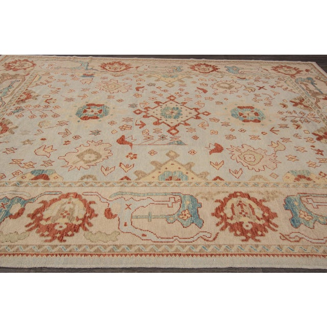 Hand-knotted rug with a floral design on a light blue field with beige borders. This rug has magnificent detailing and...