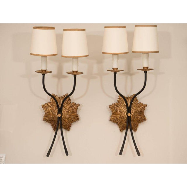 A pair of beautiful gilt iron sconces designed by Julie Neill Studio. Featuring a star-shaped backplate in a lovely warm...