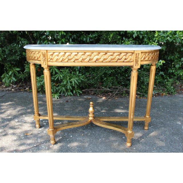 French Demi-Lune console table with Carrara marble. Made of solid oak, this piece has been newly repainted with a gold...