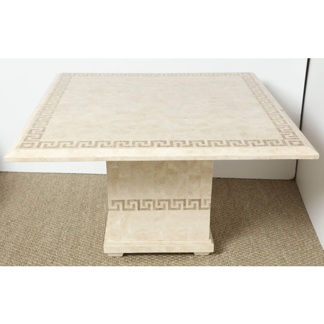 This super chic table consists of a square top with a slightly beveled edge over a square centre pedestal. It is...
