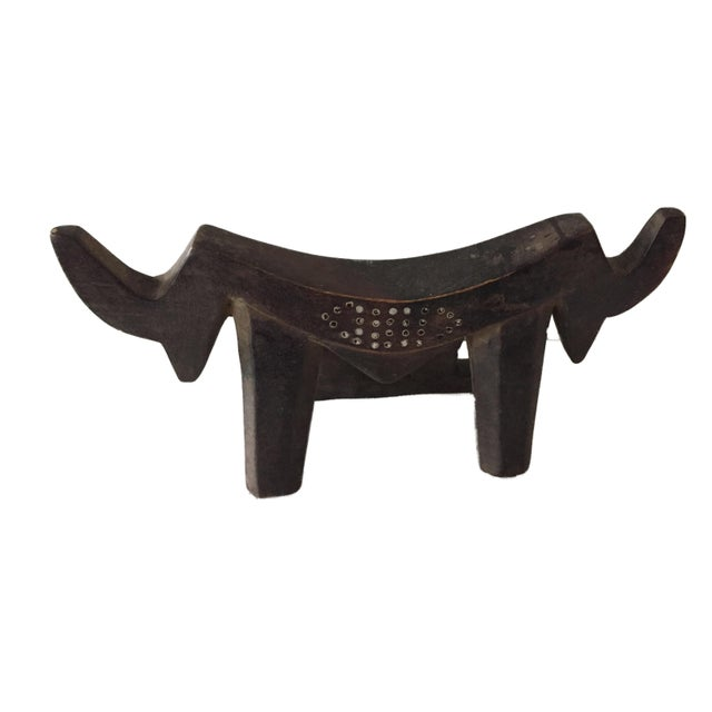 A Dinka headrest in a very stylized zoomorphic shape. The base is formed with hollow shape Each end is cut in the form of...
