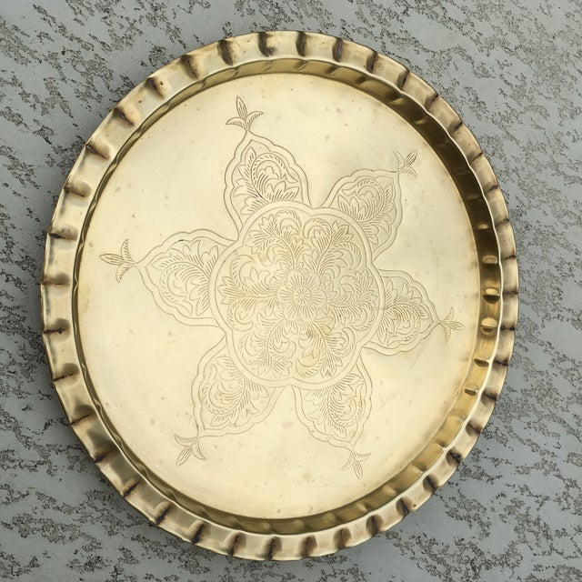 Beautiful vintage brass round tray. Has a raised border. Could be used as a table top for a small table. Love the engraved...