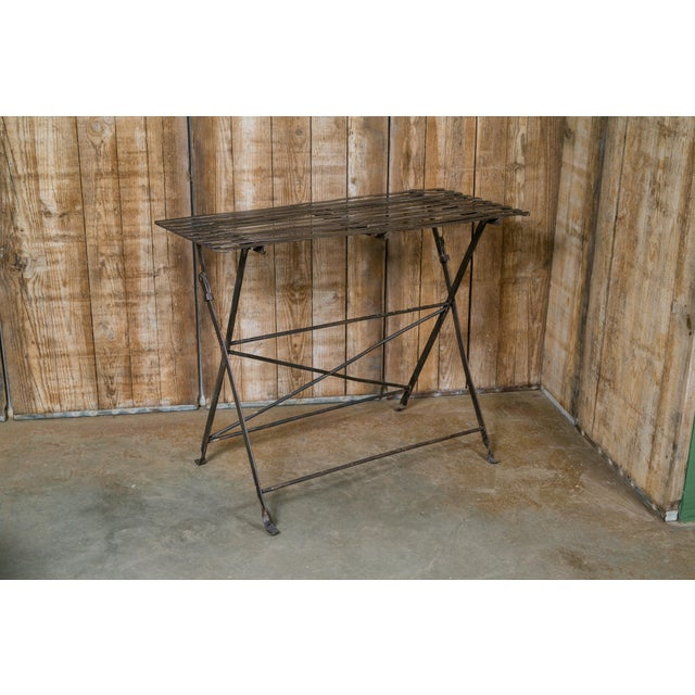 Long painted black iron rectangular table with a metal slat top. Folds up for compact storage. From France, circa 1920..