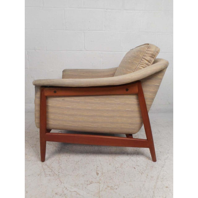 Stylish and comfortable midcentury lounge chair by DUX. The angular wooden frame with tapered legs and accents along with...