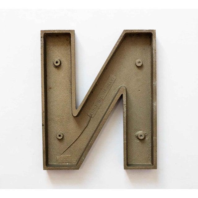 Graphic medium sized letter N in black cast metal. Vintage sign letter.