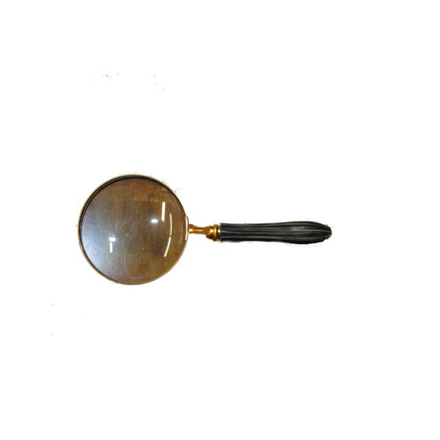 Magnifying Glass with Brass Tone Frame and Fluted Wooden Handle in Ebony Finish.