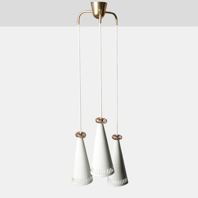 A three-pendant chandelier of brass and white enamel. Shades have a slotted metal detail and are topped with a curled...