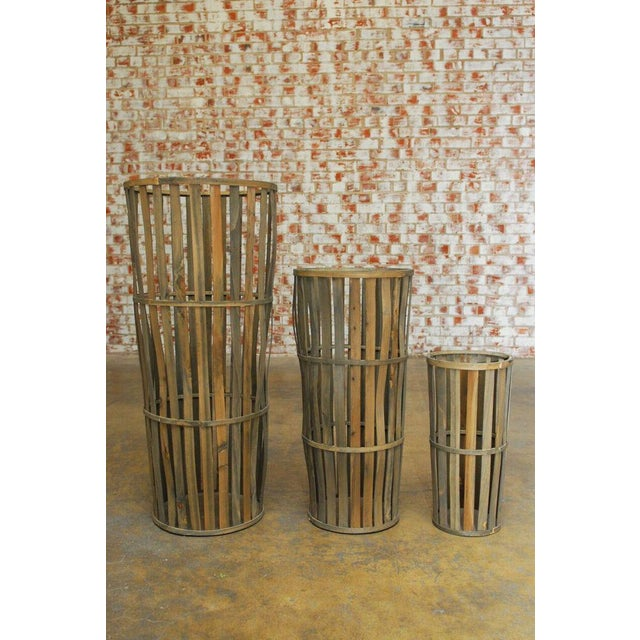 Set of three tall wooden slats make up these elongated handcrafted cellar baskets. Great for rustic home decor or...