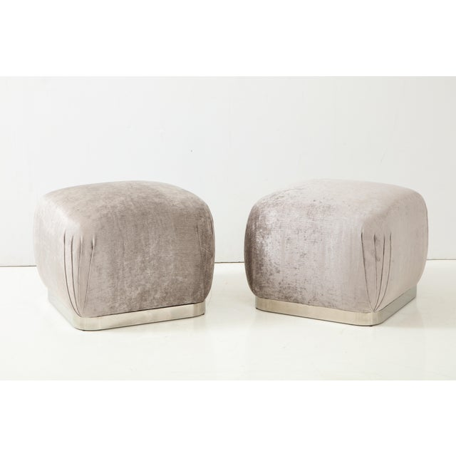 Pair of Souffle ottomans or poufs by Karl Springer. The ottomans have been newly reupholstered in a beautiful silvery grey...