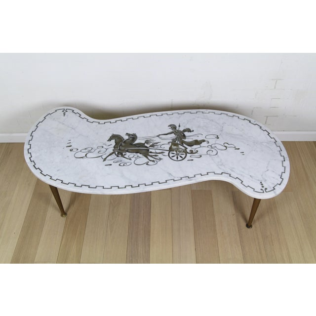 Beautiful vintage Neoclassical style coffee table. Features a Carrara marble top and a kidney shape. The marble top is...