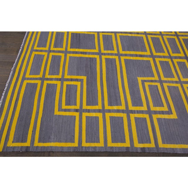 Modern handwoven Turkish Kilim rug with iconic and abstract yellow stripe design on an off-gray field. This rug measures...
