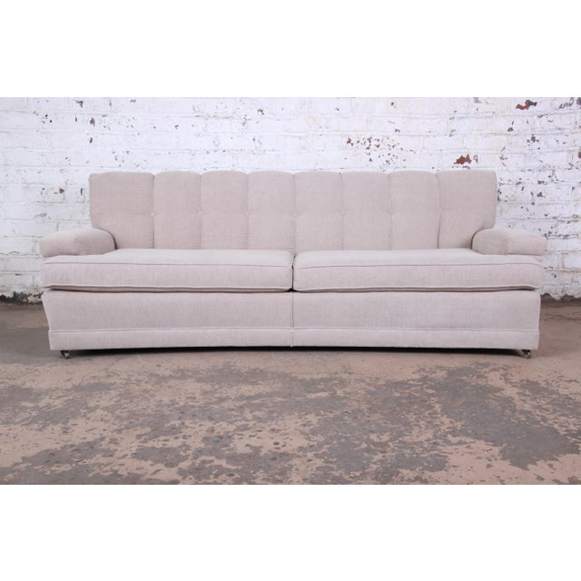 A gorgeous mid-century modern curved tufted sofa. The sofa has been newly expertly reupholstered in a nice neutral tan...