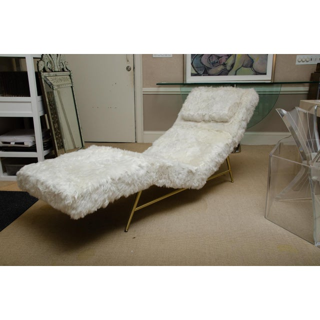 Unusual chaise covered in white rabbit with brass base designed by Milo Baughman. The chaise has a pillow also covered in...