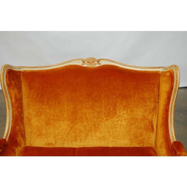 Lovely, winged, French loveseat featuring a plush, burnt orange velvet upholstery. Hand-carved frame with cabriole legs...