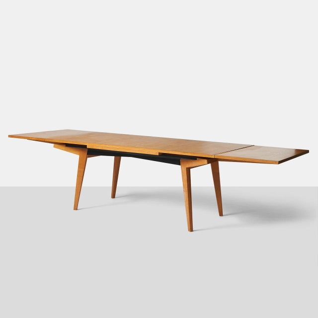 A dining table by Maxime Old in French oak with two leaves underneath that extend on each end to create a 120″ long table....