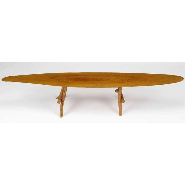 Petite Adirondack style coffee table constructed of natural wood legs and a center cut, live edge wood top.