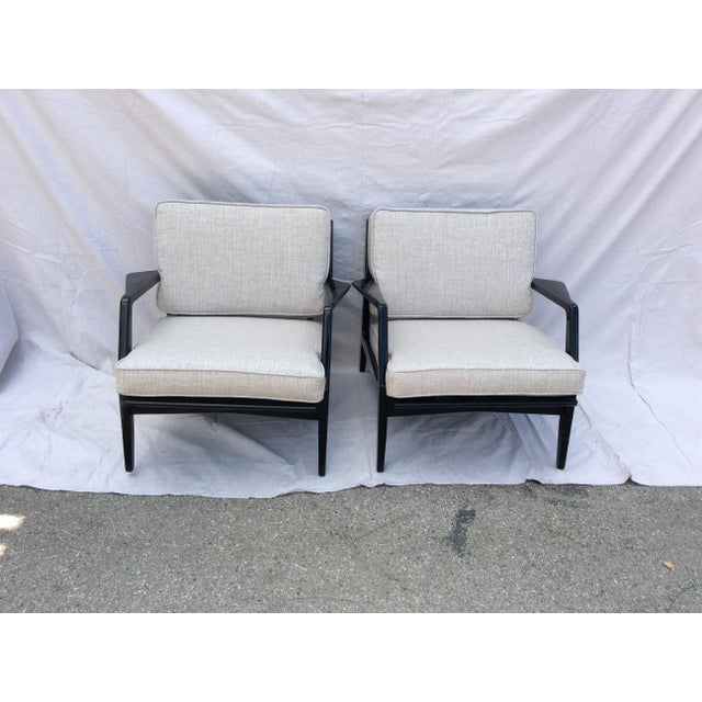 A pair of black wood mid century side chairs. The pair comes with two sets of cushions -- orange and light gray. The...
