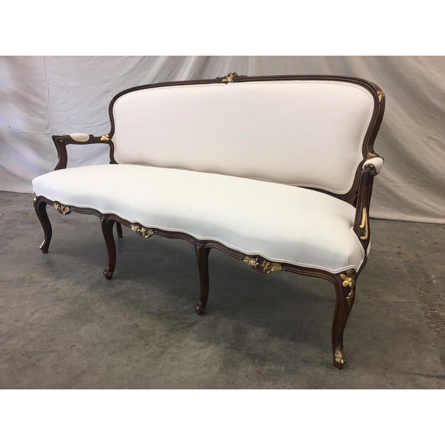 Very lovely French Louis XV style settee, newly reupholstered in an off white Belgian linen. This elegant settee has a...